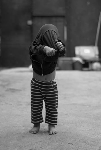 Boy removing his jacket while standing outdoors