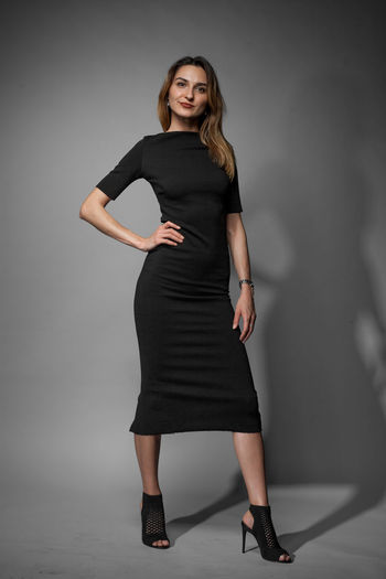 Beautiful young woman in a black dress on a gray background in the studio. Photo in full growth. Looking At Camera Fashion Portrait Beauty One Person Smiling Young Adult Beautiful Woman Front View Young Women Full Length Dress Gray Standing Gray Background Hair Women Studio Shot Adult Hairstyle