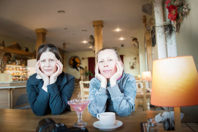 Portrait Of Friends With Hands On Chins Sitting In Cafe