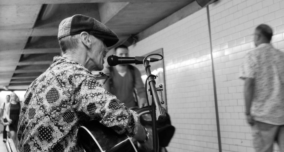 A Street Busker entertains tourists and comuters as they make their way through a London underpass at Londons Westminster Subway Busker Busking Cap Hanging Out London Music Music Man Singer  Street Streetphotography Subway Subway Station Tourism Tourist Train Station Tube Train Tube Trains
