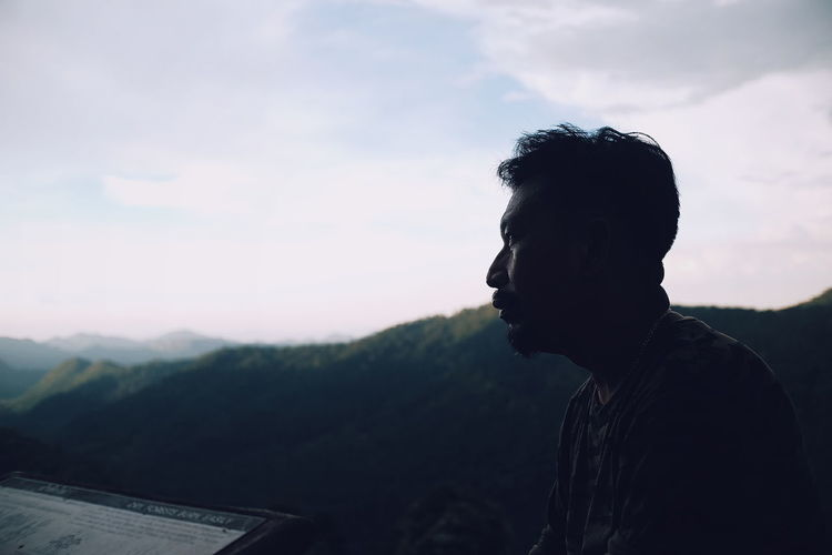 Mature man looking away against mountains