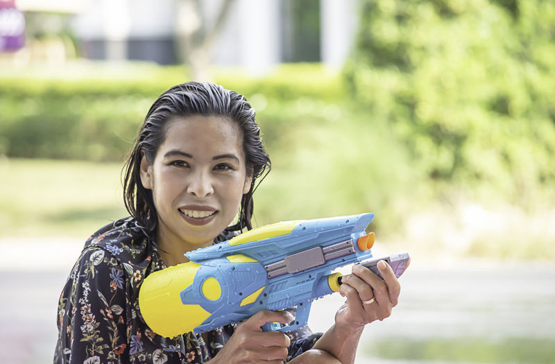 Portrait of woman holding squirt gun outdoors