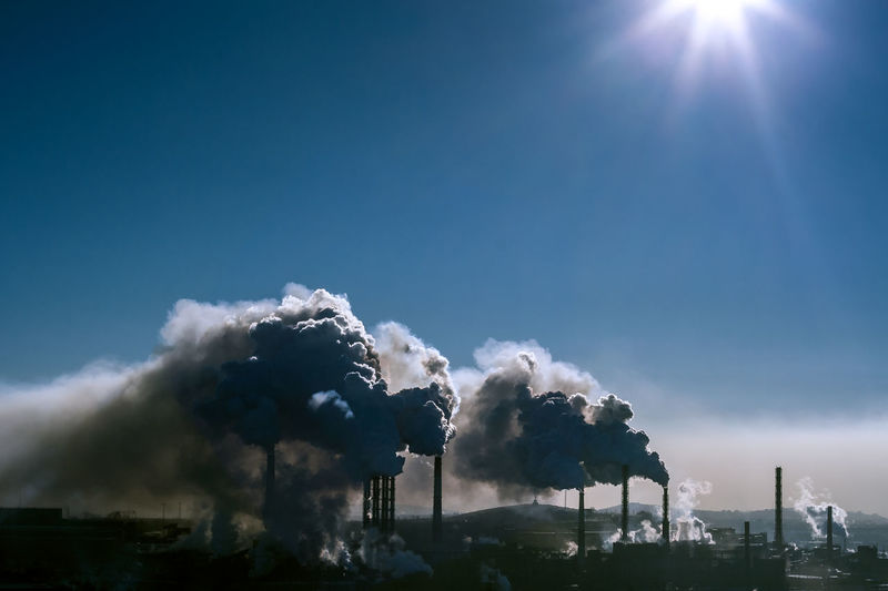 Smoke emitting from factory against sky on sunny day