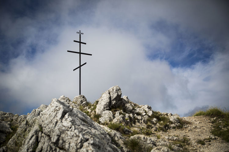 Low Angle View Of Cross On Peak Against Cloudy Sky