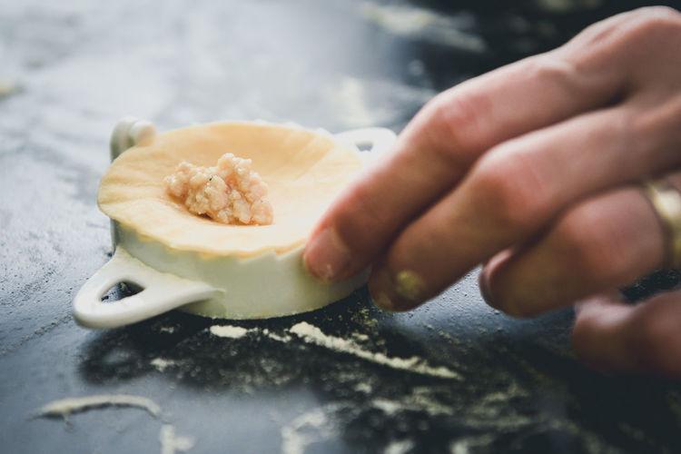 Close-up of hand holding ravioli pasta