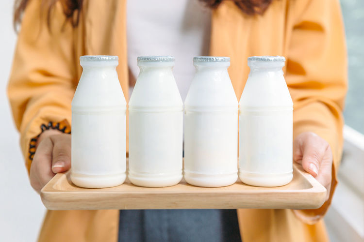 Midsection of woman holding milk bottles