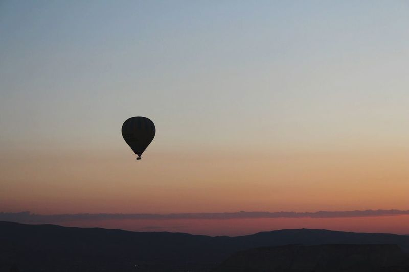 Sunset Sky Beauty In Nature Silhouette Scenics - Nature Tranquility Orange Color Tranquil Scene Nature Hot Air Balloon Mid-air Balloon Air Vehicle Transportation Flying Environment Mountain Non-urban Scene Idyllic No People