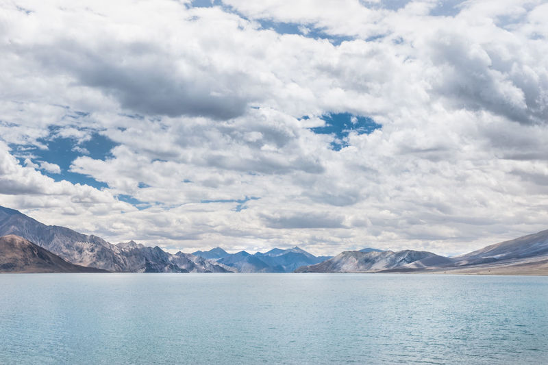 Scenic View Of Pangong Lake By Mountains Against Cloudy Sky