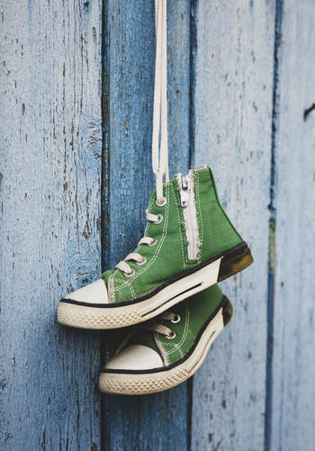 Close-up of green shoes hanging by fence