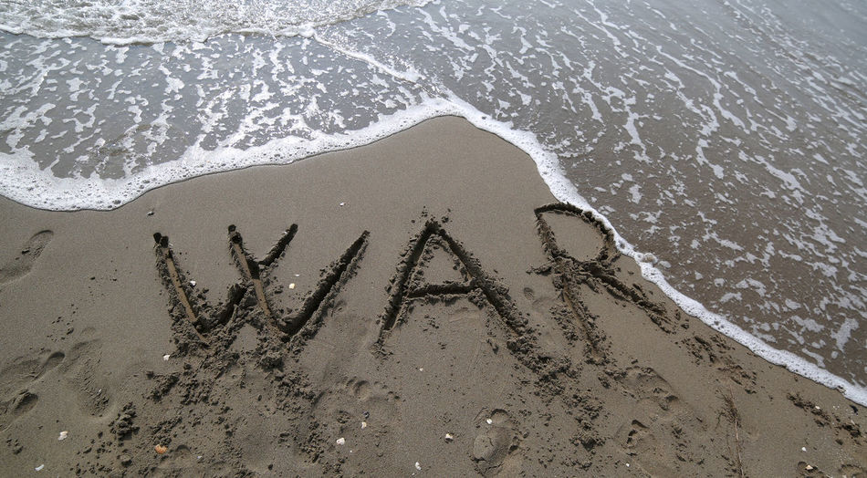 Big war text and the wave of the sea that wants to erase it on the beach