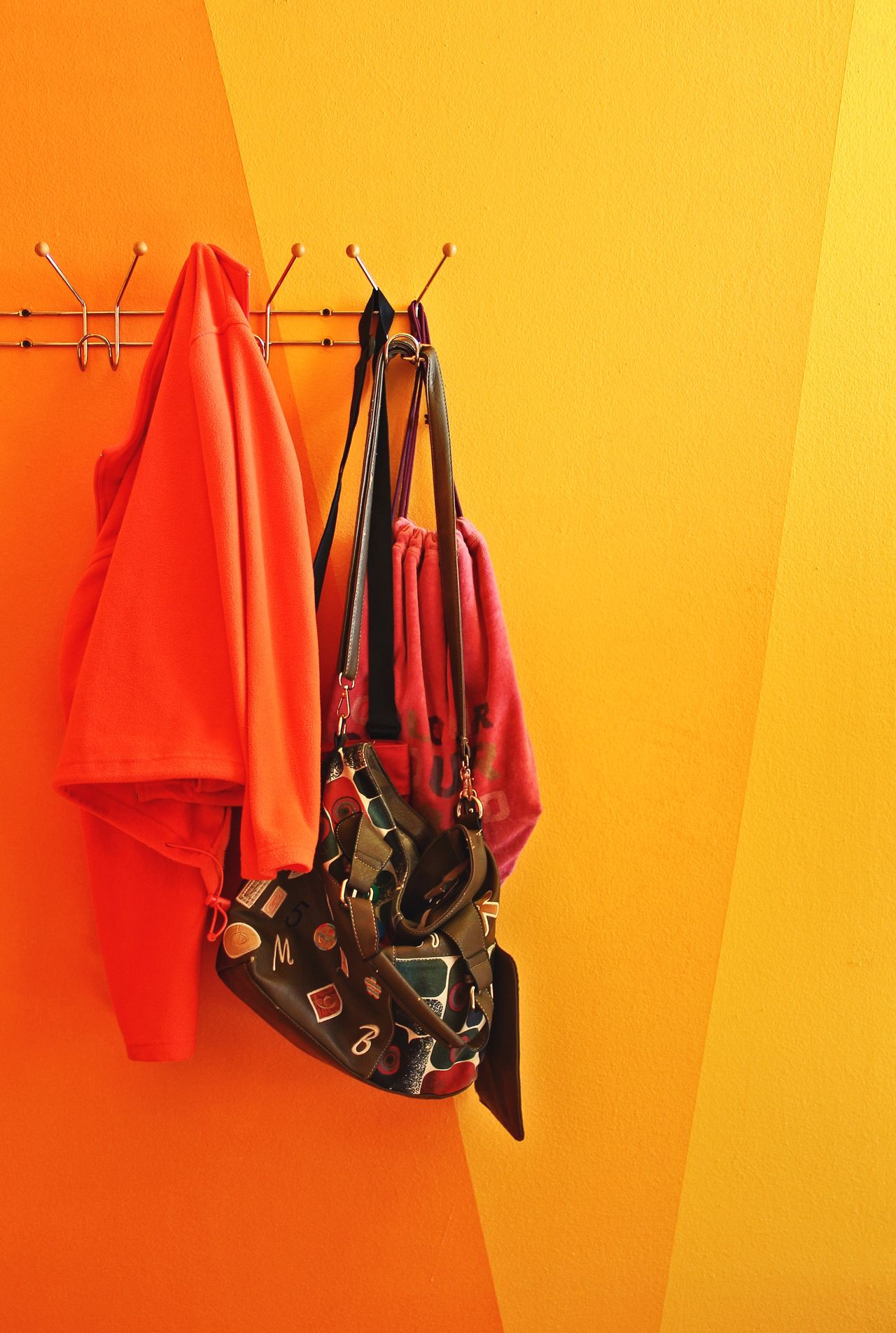 Clothes and shoulder bag hanging on yellow wall at home
