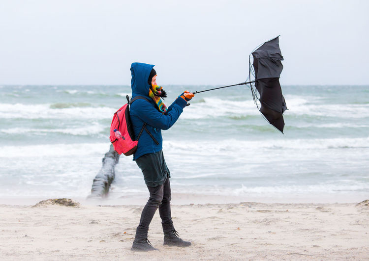Full Length Of Woman Holding Umbrella At Beach During Rainy Season