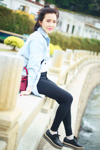 Portrait Of Young Woman Sitting On Concrete Railing