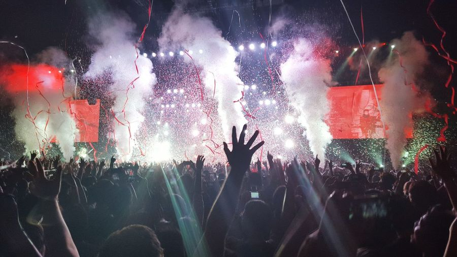 Excited fans with arms raised at concert