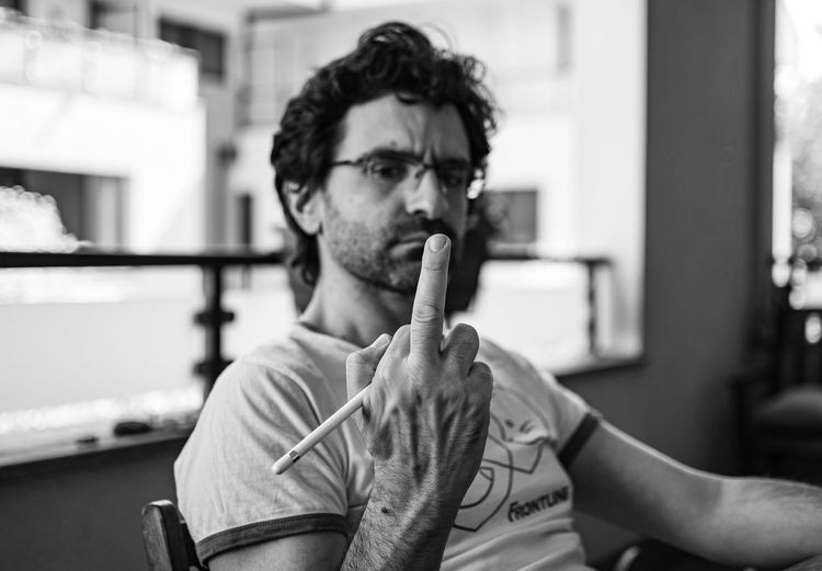 Portrait of a man making the middle finger gesture