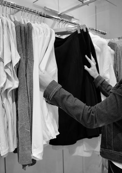 Midsection of person choosing clothes hanging on rack in store
