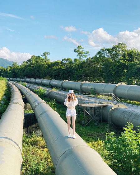 Full length of woman photographing while standing on pipes