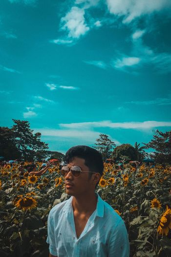 Young Man Wearing Sunglasses Looking Away While Standing On Sunflower Field