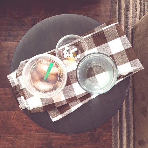 Directly above shot of pills in bowl with water on table