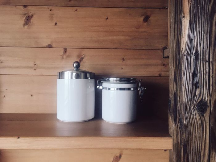 White containers against wooden wall