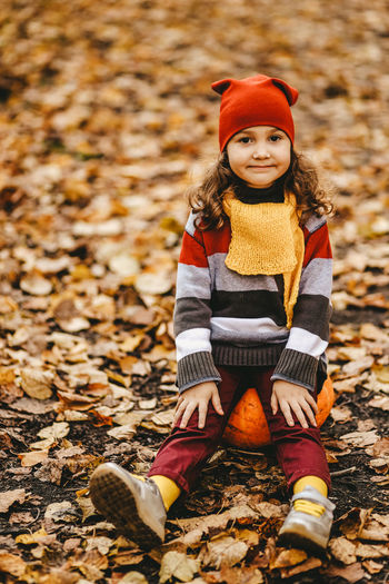 Happy cute little girl child in warm bright clothes sit on a pumpkin in the autumn forest outdoors