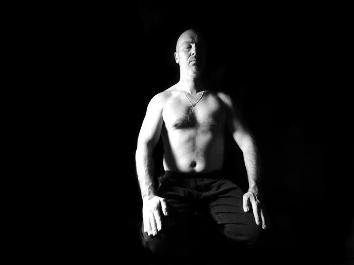 Shirtless Man Sitting With Eyes Closed Against Black Background