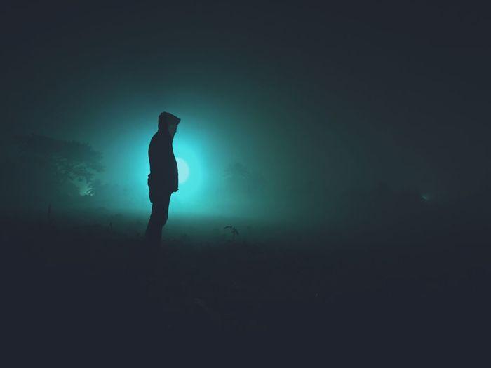 Silhouette man standing on illuminated street light against sky at night