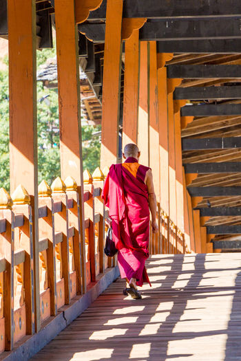 ASIA Architecture Man Punakha Punakha Dzong Architectural Column Architecture Bhutan Built Structure Clothing Culture Day Full Length History Monkey One Person Real People Rear View Religion Sunlight Traditional Clothing Walking Wood - Material