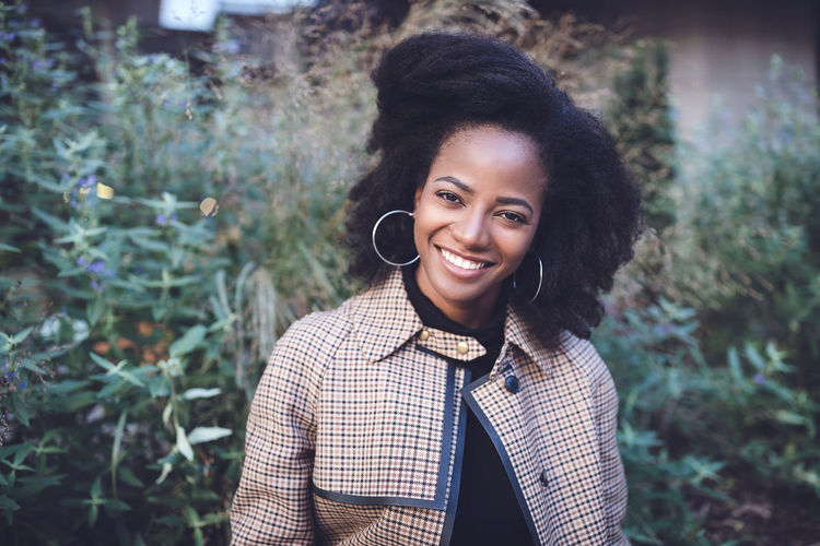 Beautiful african american young woman with afro and large hoop earrings in a stylish coat