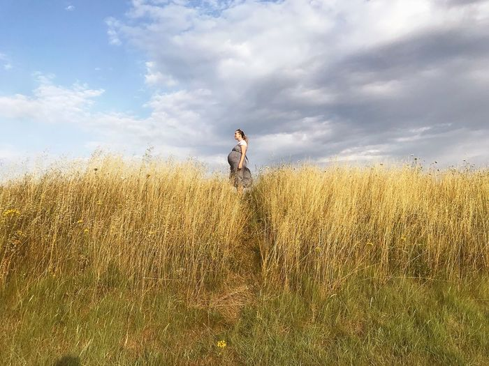 Side view of pregnant woman standing on grassy field against sky