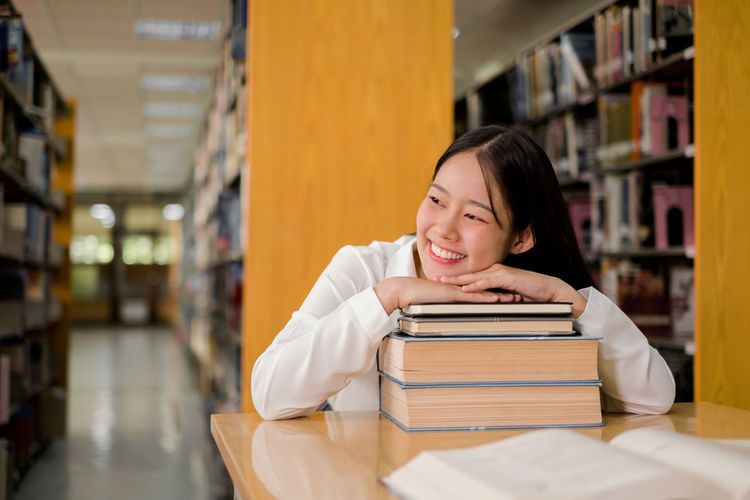 Smiling woman leaning on stacked book in library