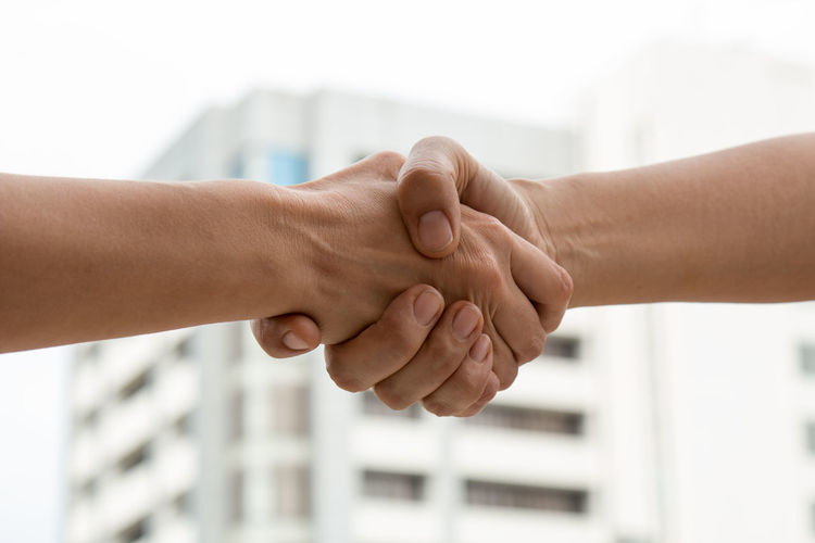 Cropped Image Of People Giving Handshake Against Building