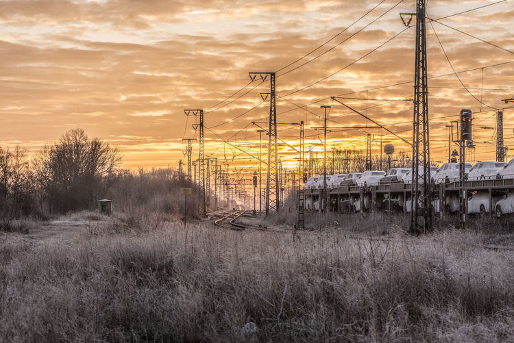 Frosty winter morning in Ostfriesland Sky Nature No People Technology Electricity  Electricity Pylon Rail Transportation Cable Grass Plant Power Line  Orange Color Power Supply Built Structure Outdoors Winter Sundawn Railway Track Car Transportation