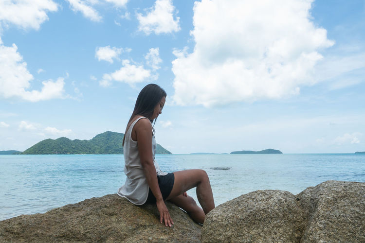 Woman sitting on rock looking at sea against sky