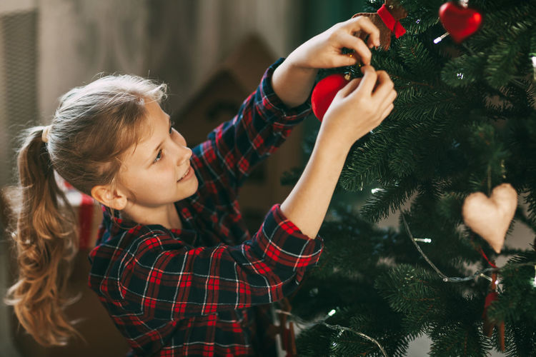 Happy little blonde in new year's home clothes, decorates the christmas tree and smiles.