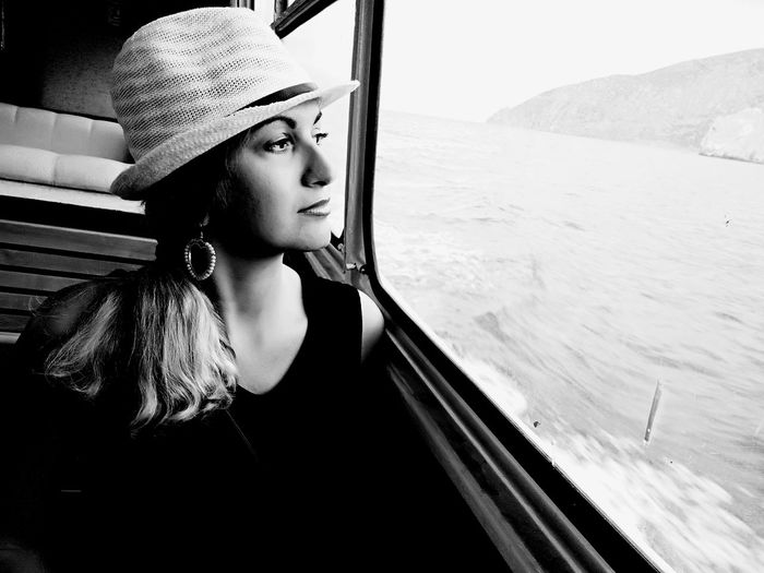 Thoughtful mid adult woman looking through window while sitting in boat