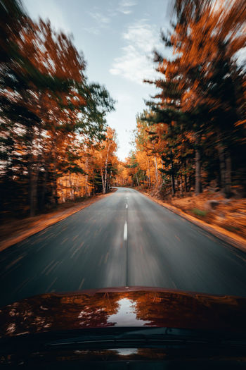 Road amidst trees seen through car windshield during autumn