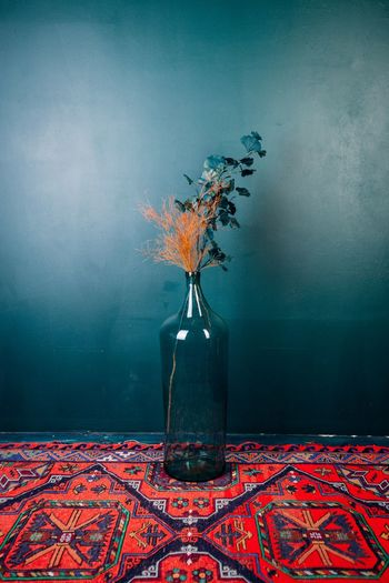 Flower vase on carpet against wall