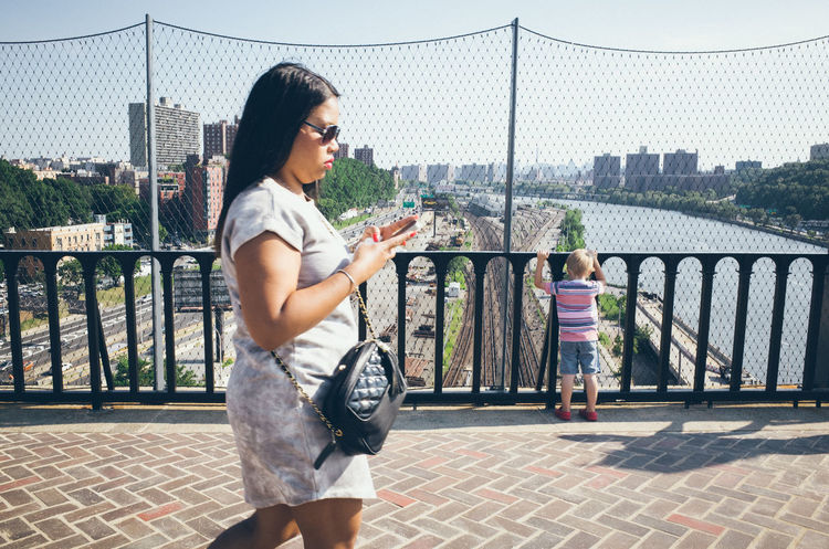 A young woman walks on the High Bridge and looks and her smartphone. Age Of Distraction Bending Over Bridge Cell Phone  Checking Composition Handy High Bridge Holding Hunching Over Lifestyles Looking At Mobile Phone New York City People Phone Preoccupied Real People Smartphone Street Photography Tech Neck Text Neck Texting Women Young Woman