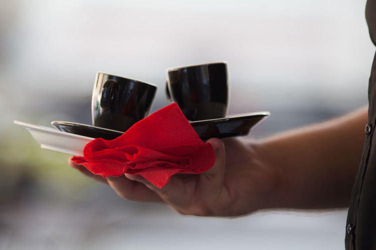 Close-Up Of Hand Holding Cups