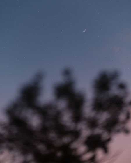 Low angle view of defocused lights against sky at night
