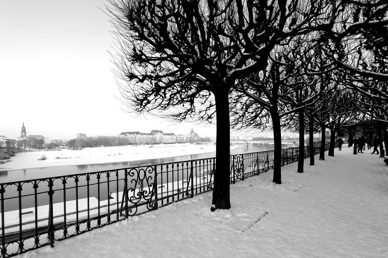 winter, snow, cold temperature, tree, railing, bare tree, outdoors, nature, built structure, architecture, building exterior, no people, bridge - man made structure, day, water, sky, branch, beauty in nature, city