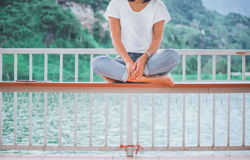 Low section of woman sitting on bench against railing