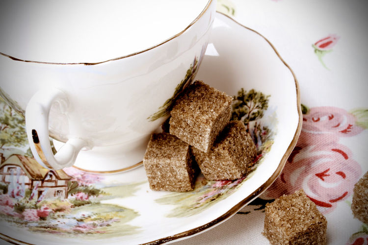 Close-up of brown sugar by cup on saucer