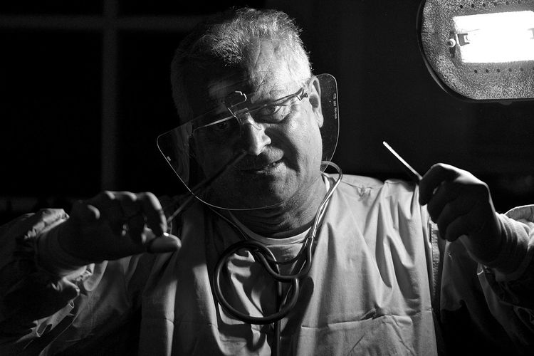 Portrait of doctor working in dark operating room