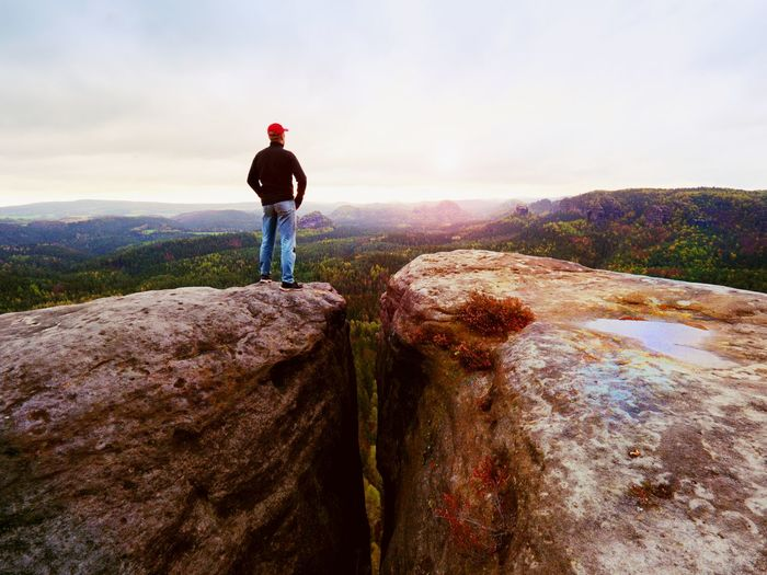 Man in jeans black outdoor sweatshirt and red cap stay at the end of cracked rocky cliff.