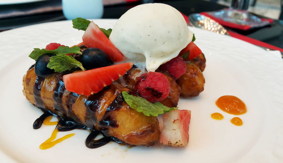 Close-Up Of Fried Banana With Fruits And Ice Cream On Plate