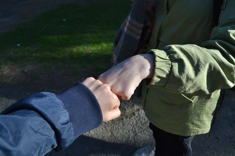 Midsection of friends fist bumping on footpath during sunny day
