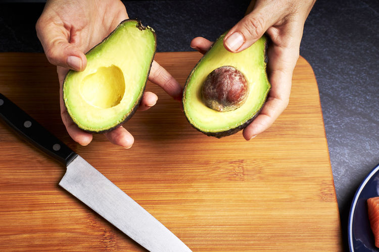 Cropped image of person preparing food on cutting board