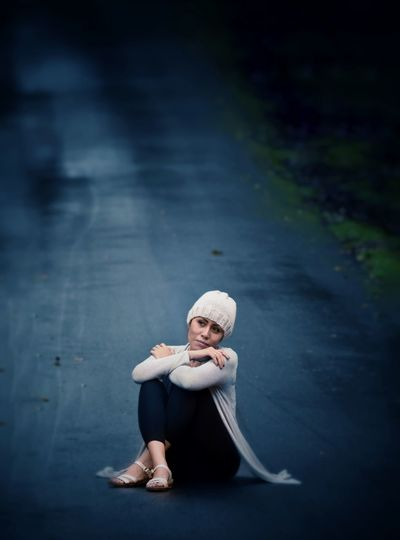 Full length of thoughtful mature woman looking away while sitting on road